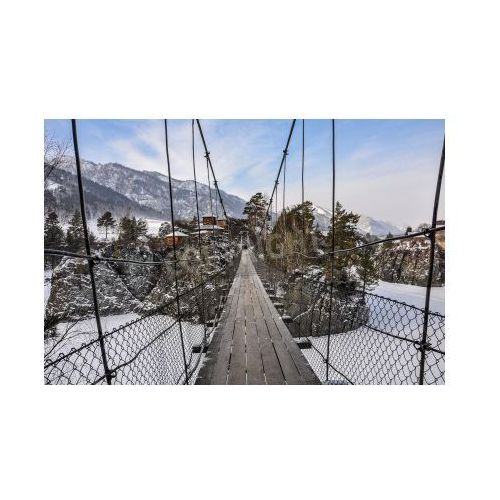 Fototapeta suspension footbridge to the church across the frozen river in winter mountains